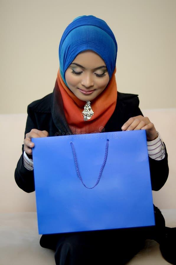 Muslimah bedrijfsvrouw in hoofdsjaal met het winkelen zak stock foto's