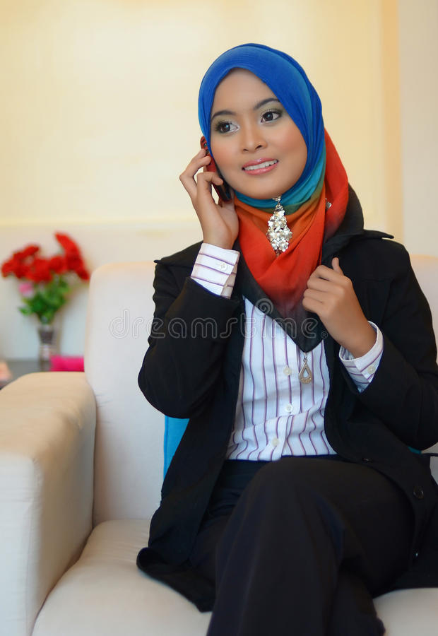 Muslimah business woman talking on cell phone royalty free stock image