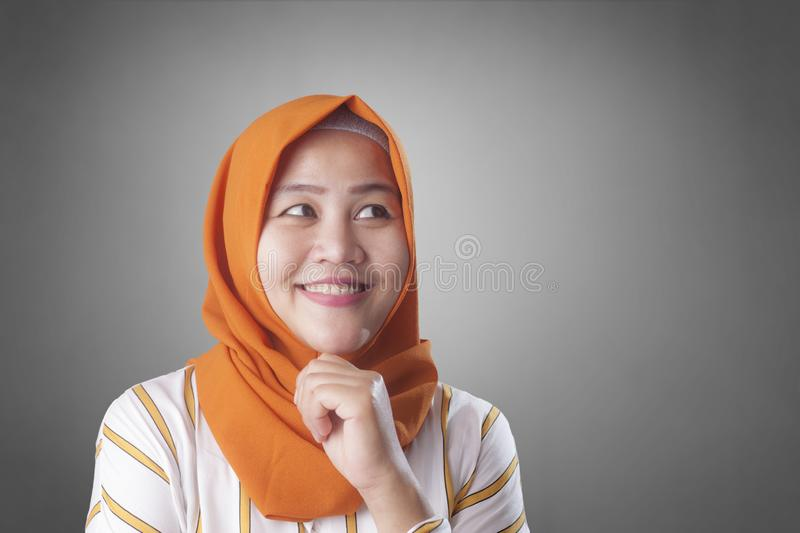Muslimah Businesswoman Thinking Something, Having Bright Idea. Asian muslim businesswomen wearing hijab with curiousity thinking expression. Having good idea royalty free stock image