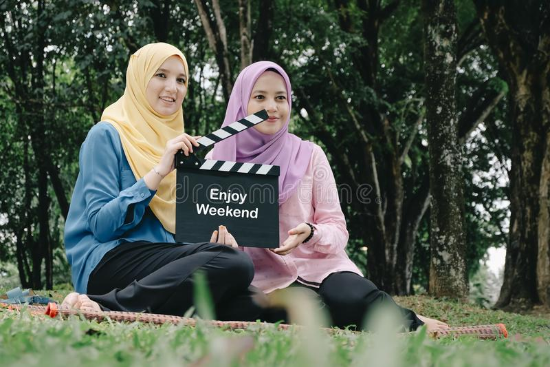 Muslimah holding professional film slate with word ENJOY WEEKEND, movie clapper board at park. Young and attractive muslimah holding professional film slate with stock photo