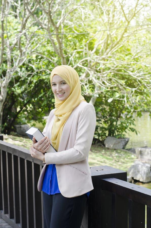 Muslimah kvinnaanseende och hållande anteckningsböcker royaltyfria foton