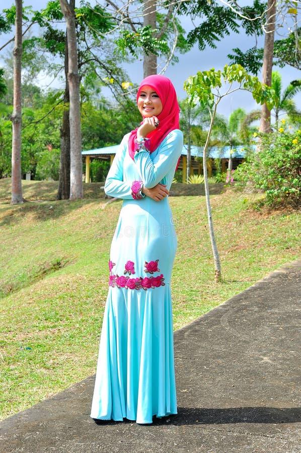 Muslimah lady wear blouse and hijab. Beautiful muslimah lady wear blouse and hijab posing at garden stock photo