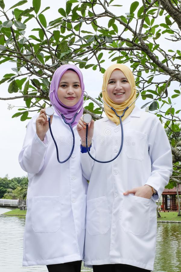 Muslimah medical practitioner posed with their stethoscope at pa. Rk during lunch hour royalty free stock photography