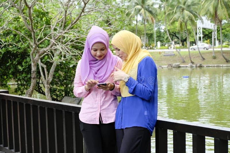 Muslimah openlucht genieten van, hebbend bespreking bij park en één van hen holdings mobiele telefoon stock afbeelding