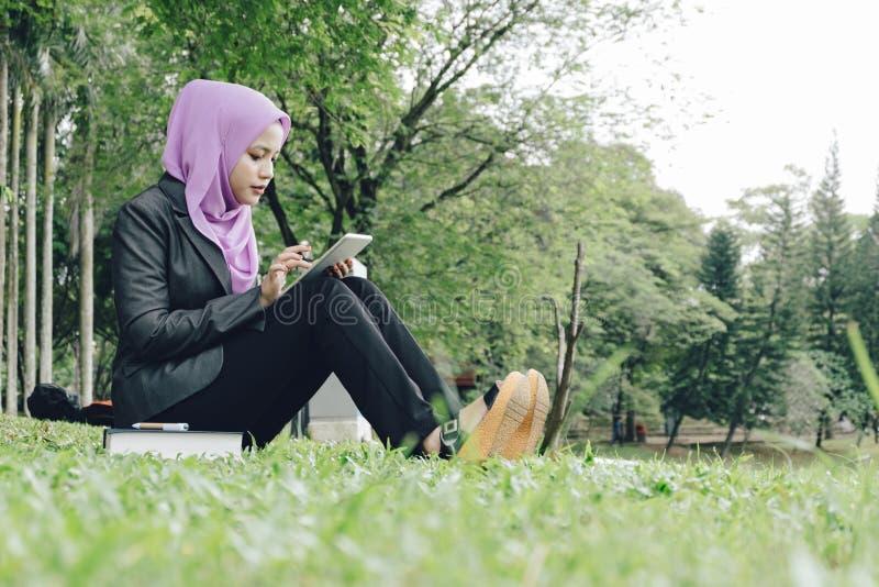 Muslimah student som läser en eBook på hennes minnestavla royaltyfria bilder