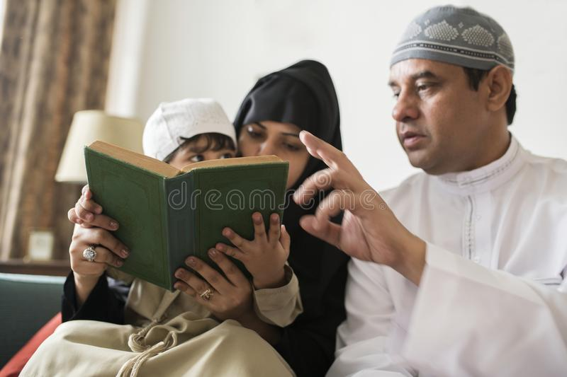 Muslims family reading the Quran together at home stock photos