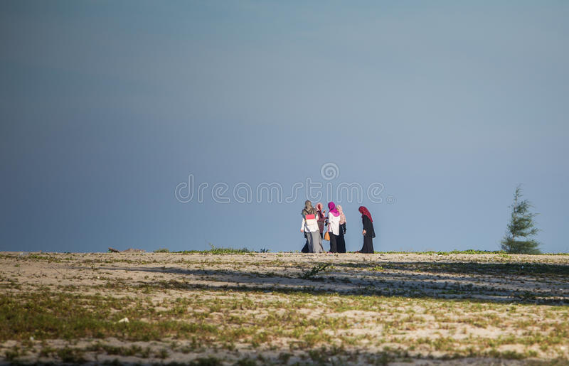 Muslims women on the beach. Terengganu, Malaysia - 23 March 2015: Muslims women seen at Batu Buruk Beach in Terengganu royalty free stock images