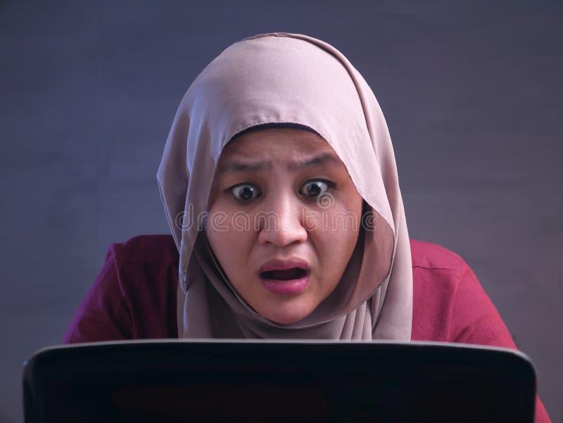 Muslimsk aff?rskvinna Working p? chockad bed?vad gest f?r b?rbar dator arkivbild