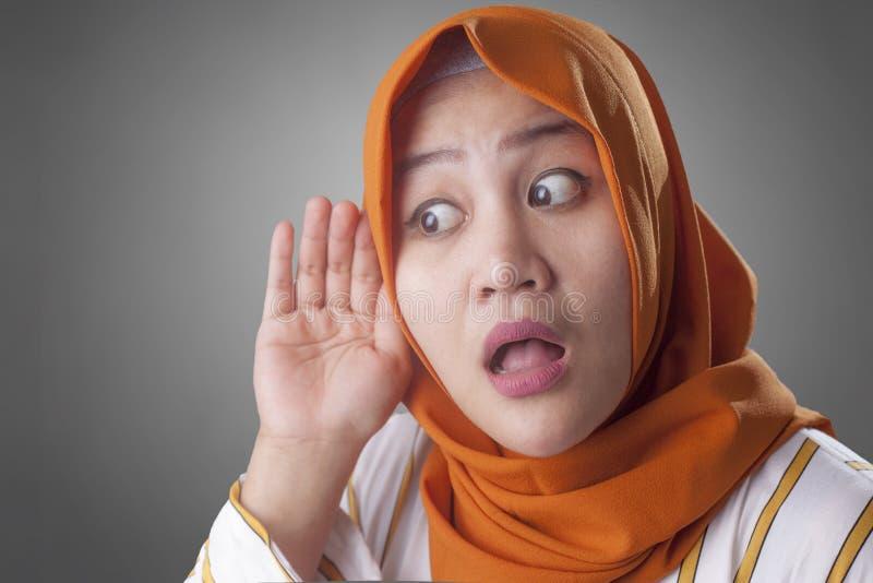 Muslimsk dam, i att lyssna f?rsiktigt, hand p? ?rat royaltyfria bilder