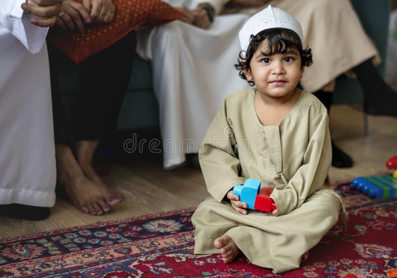 Muslimsk familj som hemma kopplar av och spelar arkivbild