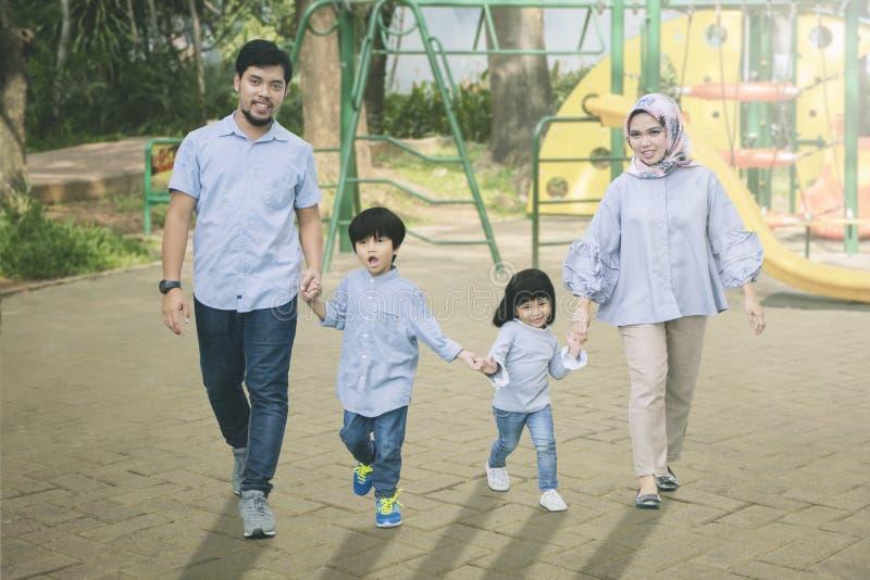 Muslimsk familj som tillsammans spelar i lekplatsen arkivfoto