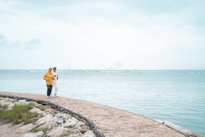Muslimsk gammal pargenomkörare och spring på stranden arkivfoto