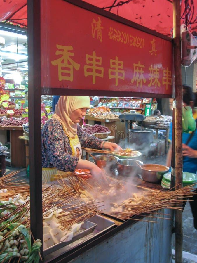 Muslimsk kines från den Hui person som tillhör en etnisk minoritet som lagar mat buntar av köttsteknålar på Beiyuanmen den muslim arkivbilder