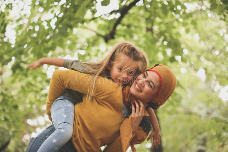 Muslimsk kvinna med barnet som utanför spelar På flyttningen royaltyfria foton