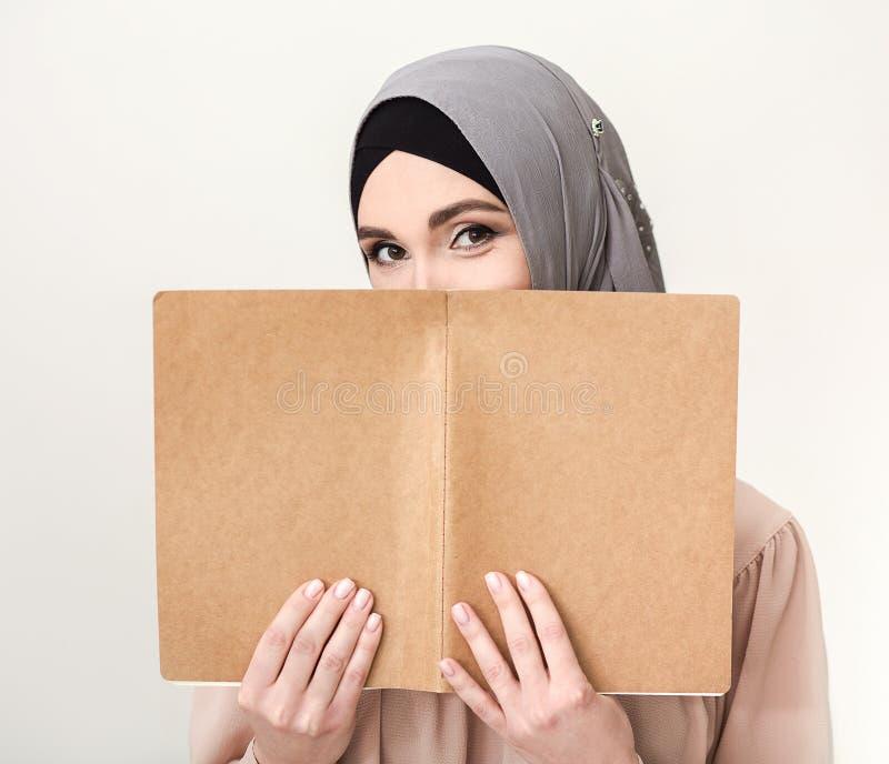 Muslimsk kvinna med bokståenden royaltyfria foton