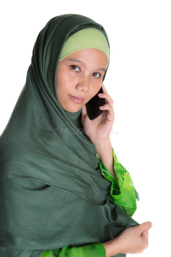 Muslimsk kvinna med den Smartphone droppen royaltyfri foto