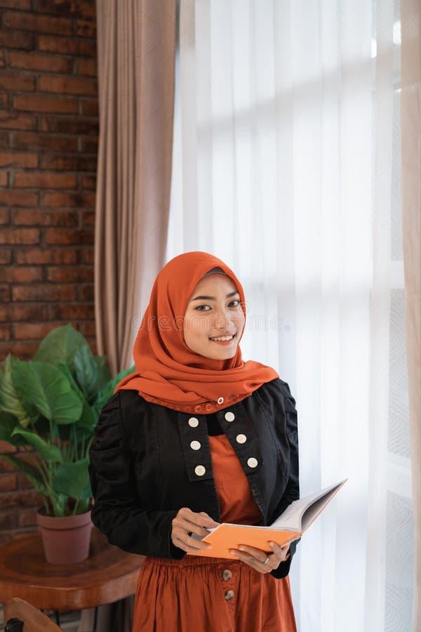 Muslimsk kvinna med huvudhalsduken som läser en bok royaltyfri bild