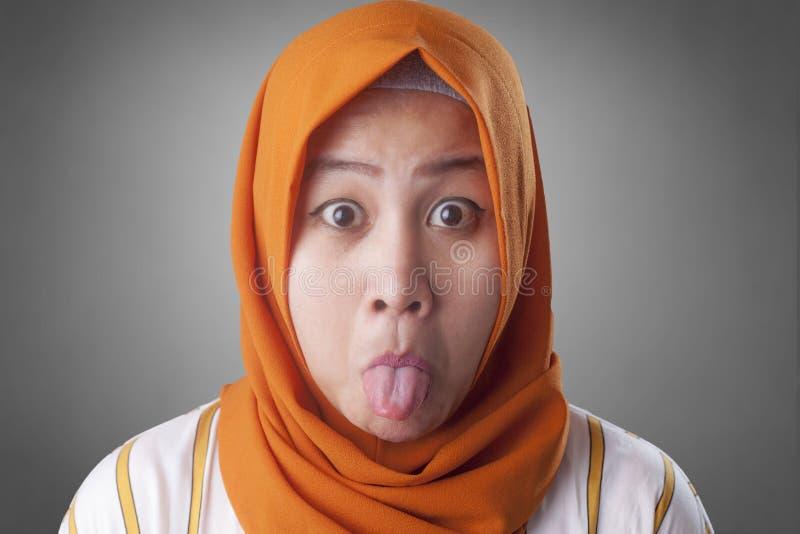 Muslimsk kvinna med tungan ut royaltyfria bilder