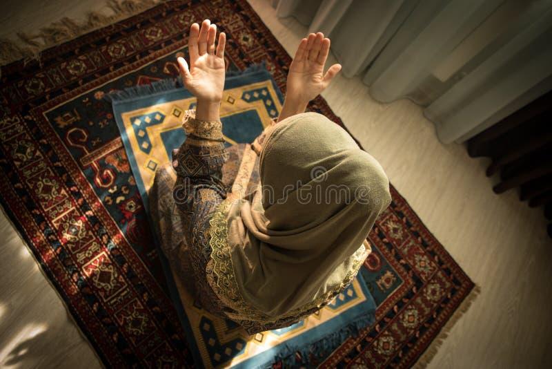 Muslimsk kvinna som ber för Allah muslimgud på rum nära fönster Händer av muslimkvinnan på mattan som ber i traditionellt bära arkivbilder
