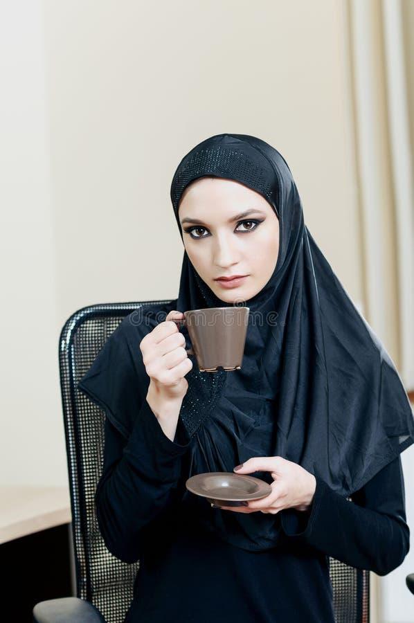 Muslimsk kvinna som dricker kaffe, medan sitta i en kontorsstol arkivfoton