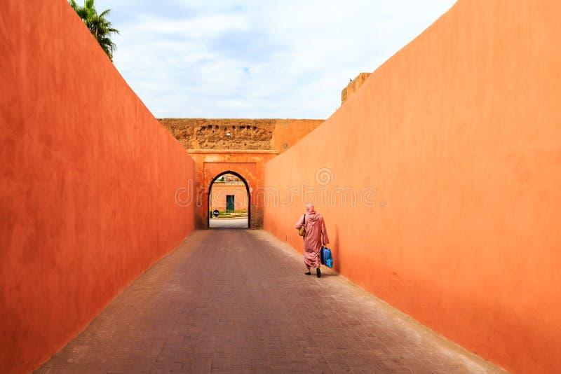 Muslimsk kvinna som går till och med en smal gata med porten i Marrak royaltyfri fotografi