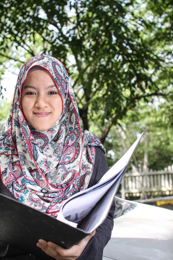 Muslimsk kvinna som rymmer en mapp fotografering för bildbyråer