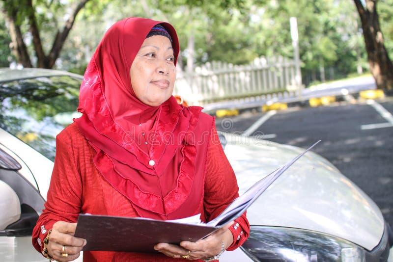 Muslimsk kvinna som rymmer en mapp royaltyfri fotografi