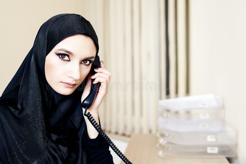 Muslimsk kvinna som talar på en landlinetelefon arkivbild