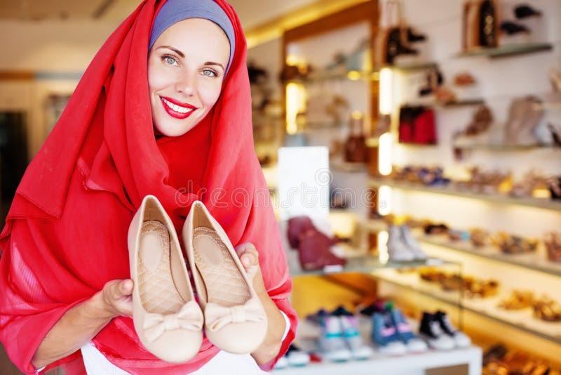 Muslimsk kvinna som väljer skor i en shoppa arkivfoton