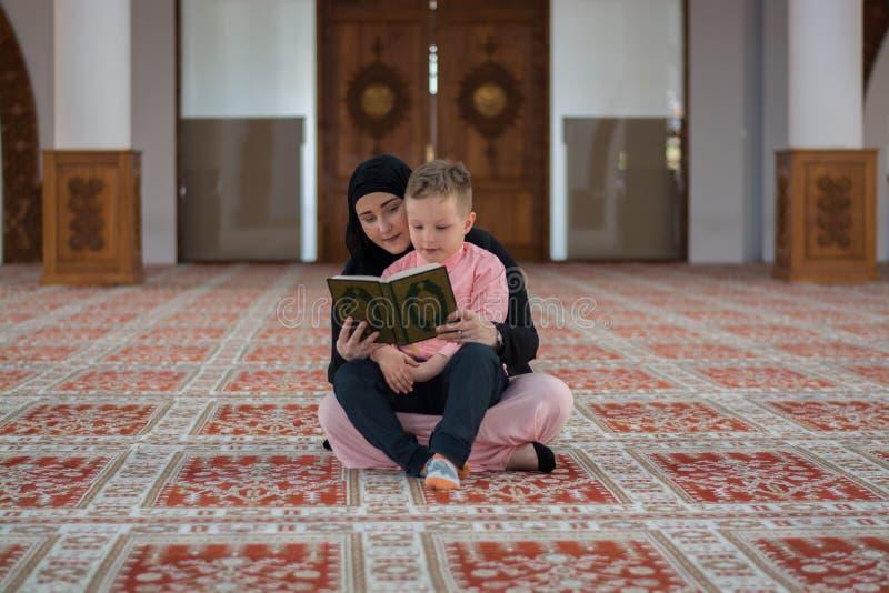 Muslimsk läs- Koranen för kvinna och för son, muslimfamilj royaltyfria bilder