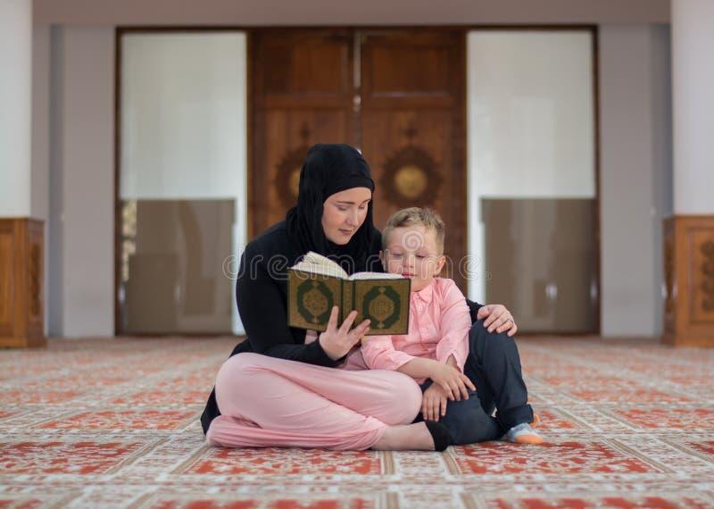 Muslimsk läs- Koranen för kvinna och för son, muslimfamilj arkivfoton