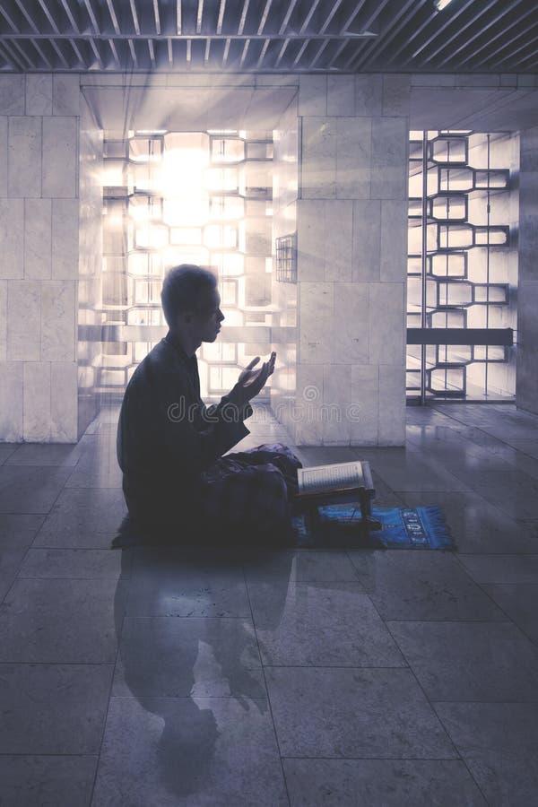 Muslimsk man som ber till Allahen i moské fotografering för bildbyråer
