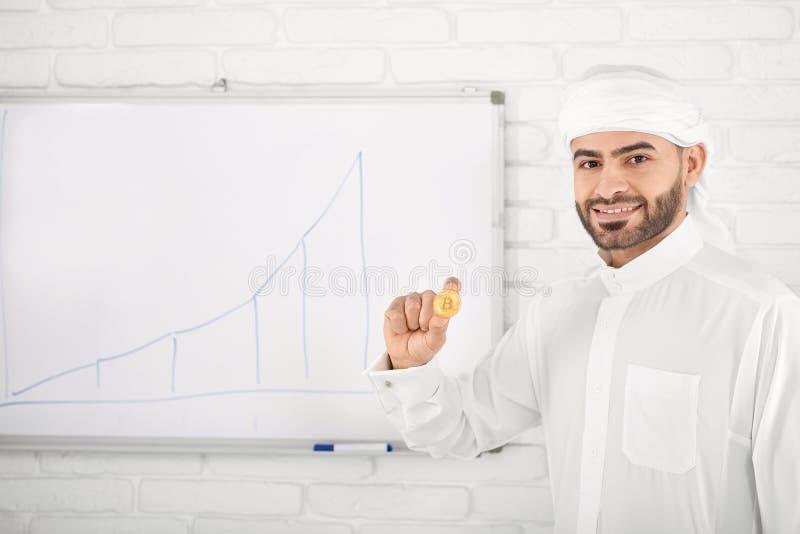 Muslimsk manlig modell i traditionella islamiska kläder som rymmer guld- bitcoin som framme poserar av finansdiagram royaltyfria foton