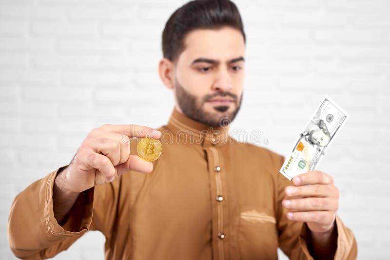 Muslimsk manlig modell i traditionella islamiska kläder som ser hundra dollar, medan rymma guld- bitcoin i hans händer arkivbild