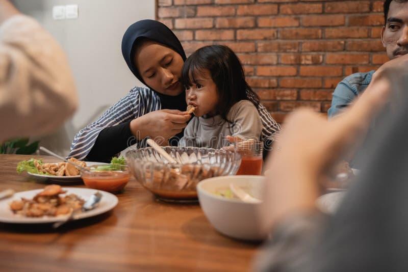 Muslimsk moder som matar hennes litet barnbarn under matställe arkivbild
