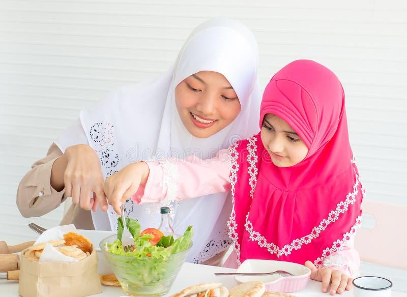 Muslimsk moderpunkt till grönsaksallad, medan lilla flickan med rosa hijab har gyckel med pålagd blandande sallad tabellen royaltyfri foto