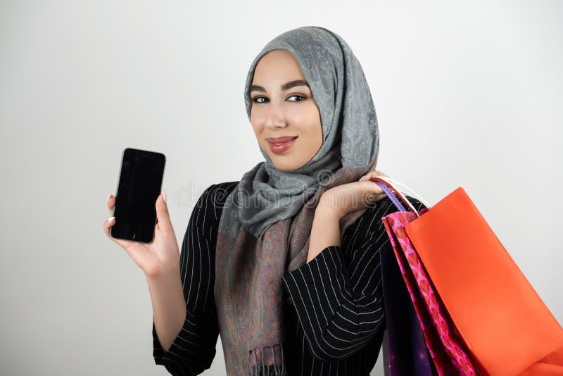 Muslimsk smartphone för visning för sjalett för hijab för turban för affärskvinna bärande med en hand och bärande shoppingpåsar i arkivfoto