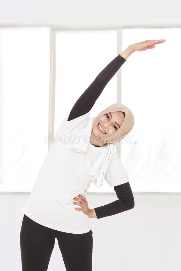 Muslimsk sportig kvinna som gör kropp- och handsträckning royaltyfria foton