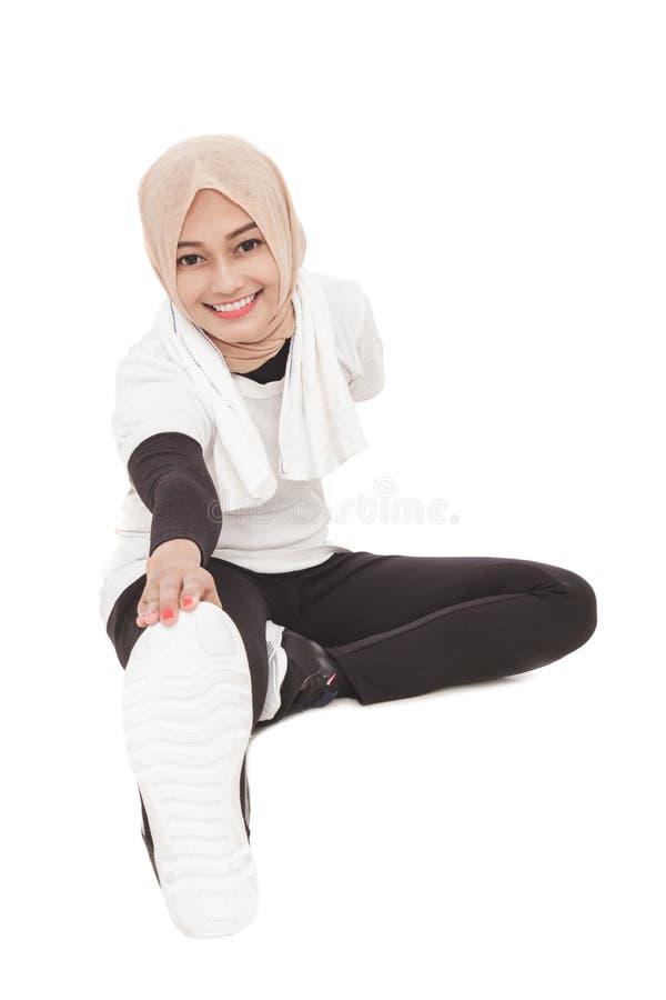 Muslimsk sportig kvinna som värmer upp för genomkörare arkivfoton