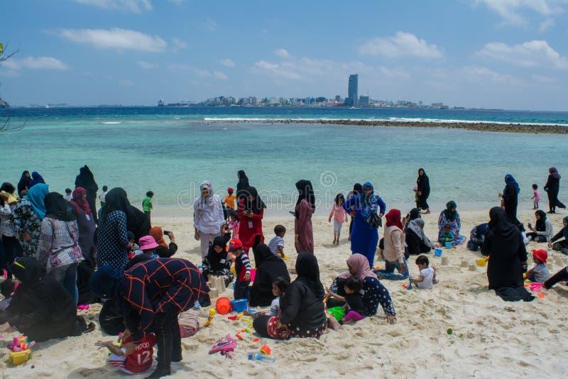 Muslimska familjer som kopplar av på den tropiska stranden i Maldiverna royaltyfri bild
