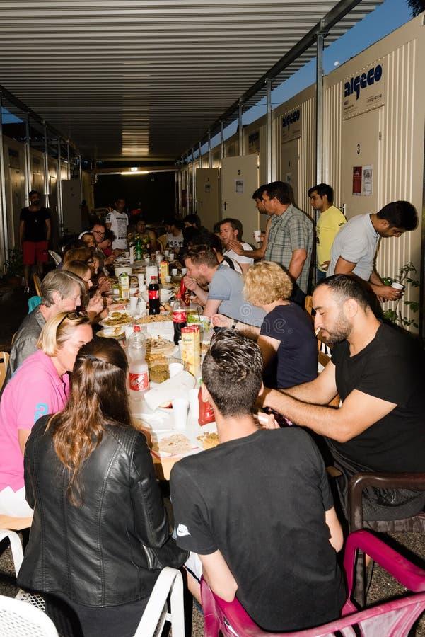 Muslimska flyktingar och tyska volontärer sitter äta tillsammans matställen under fasta månad för Ramadan arkivbild
