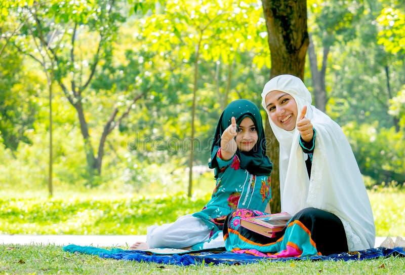 Muslimska kvinna- och flickashowdunsar upp till kameran under att läsa några böcker i trädgården arkivbild