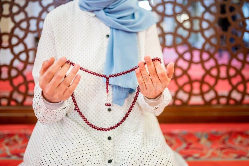 Muslimska kvinnah?nder, medan rymma radbandet och att be fotografering för bildbyråer