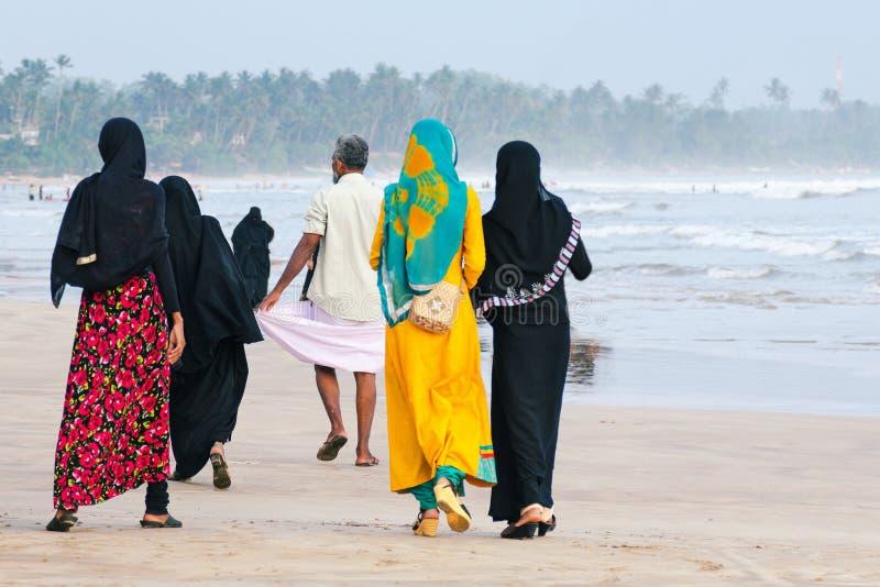 Muslimska kvinnor promenerar stranden, en man går framåt royaltyfri fotografi