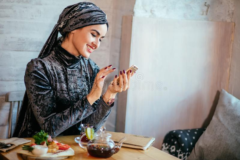 Muslimska kvinnor som rymmer smartphonephone tänka av bra minnen royaltyfria foton