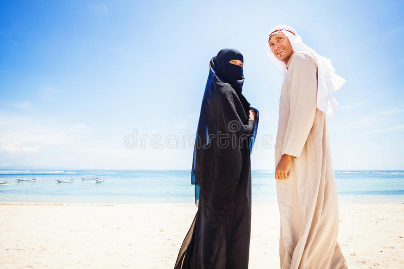 Muslimska par på en strand royaltyfria foton