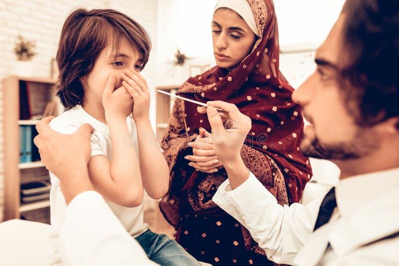 Muslimska pediatriska Examining Boy, sjuk hals arkivfoton