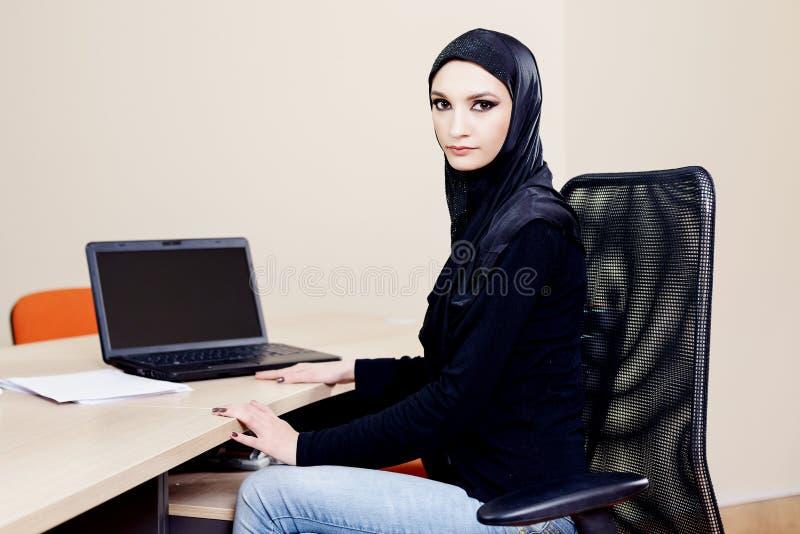Muslimskt sammanträde för hijabwearerkvinna på ett skrivbord med en dator arkivfoto