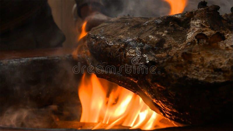 Muslo asado a la parrilla y ahumado del cerdo en parrilla profesional Asado a la parilla del jamón de Praga con el bornfire foto de archivo libre de regalías