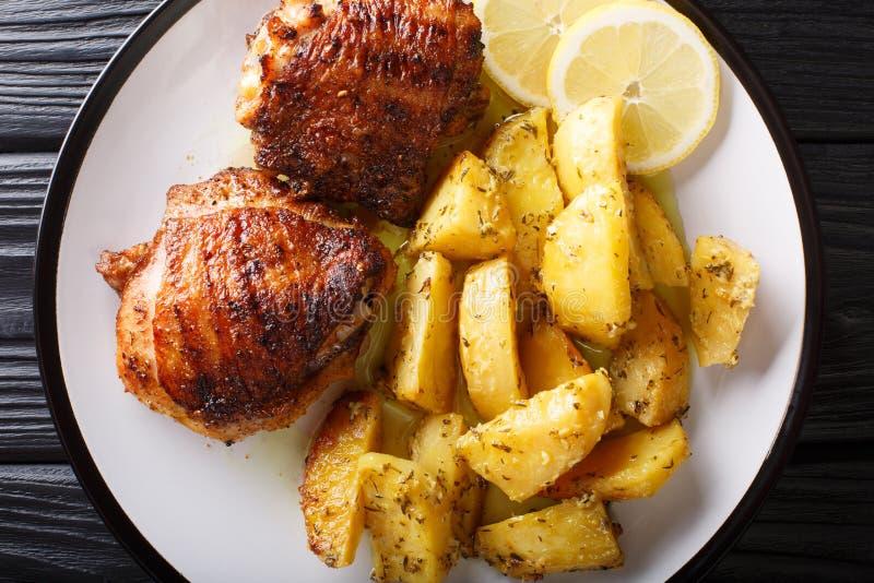 Muslos griegos del pollo de la comida asados a la parrilla con el primer frito de las patatas del or?gano del ajo del lim?n visi? imagen de archivo